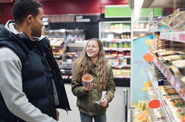 young girl buying soup in supermarket