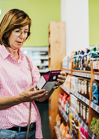 Mature Woman Reading Label On Food Items in supermarket