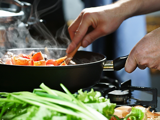 man cooking vegetables in a pan