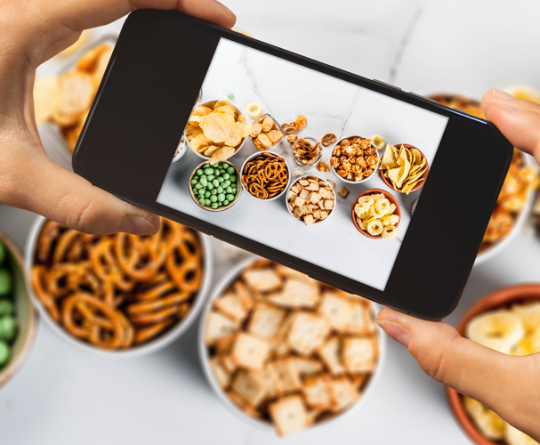 Close up of hands holding smartphone and taking a picture of a snacking table