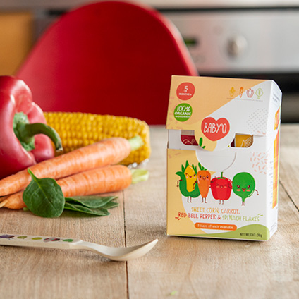 Baby food infant cereals with vegetables on wooden table