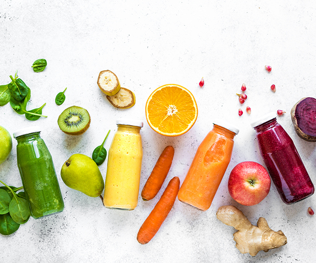 Various colorful smoothies or juices in bottles and ingredients on white
