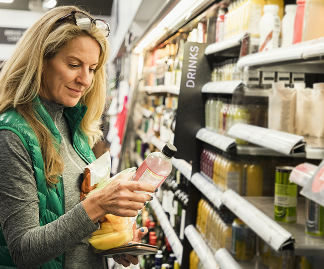A front-view shot of a mature caucasian woman shopping for a healthy snack in a supermarket