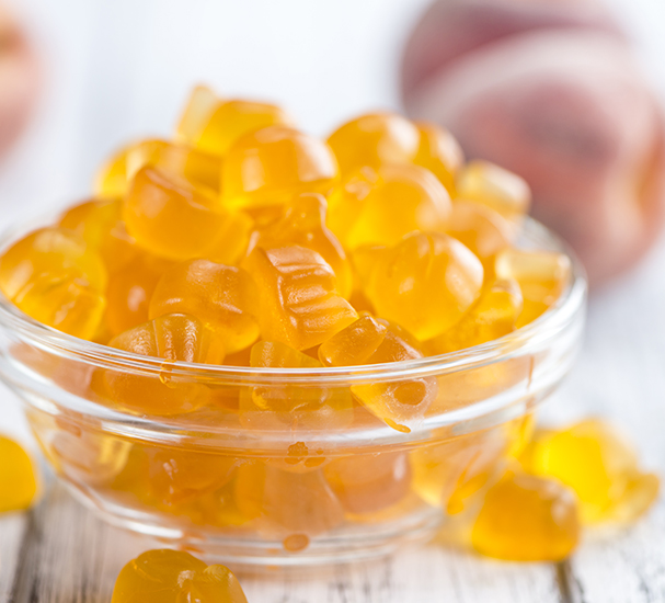 Close up of orange gummies with peach on table