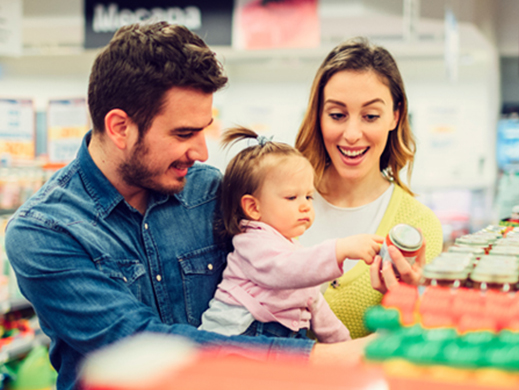 Parents buying baby food with their child in supermarket