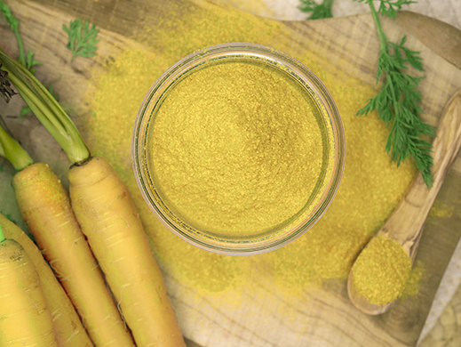 Top view of yellow carrot powder with raw carrots on table