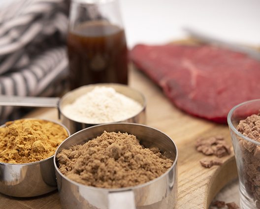 Beef ingredients in pans with flank steak in background