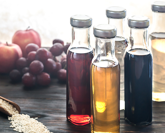 Various vinegars bottles with apples and grapes in background