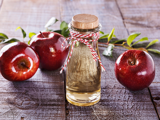 Apple cider vinegar bootle with apples background