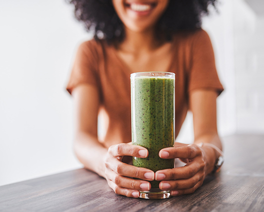 Afro smiling woman with hands around a glass of an healthy green detox beverage