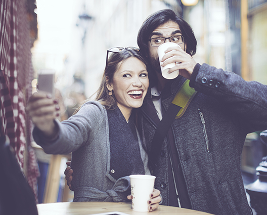 Happy and smiling couple taking selfie at coffee shop table in streets