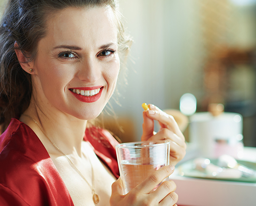 Smiling woman holding capsule and glass of water